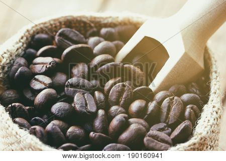 Coffee beans in gunny sack under sun light. Close up of coffee beans concept for background and wallpaper. Macro concept of roasted black coffee beans for background and texture. Rustic bag fulled with coffee beans.