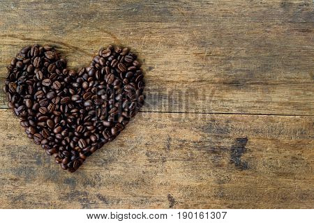 Heart shape from coffee beans. Lovely heart shape by roasted coffee beans on rustic wood table. Love theme concept with coffee beans for Valentine's background and. Old wood with copy space and coffee bean in heart shape for love theme.