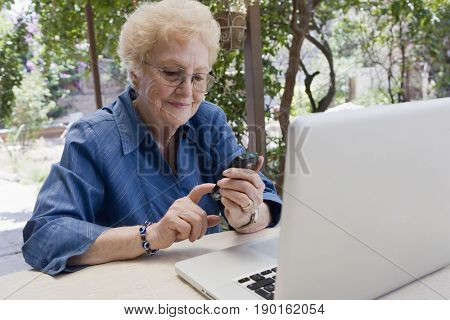 Older Hispanic woman using cell phone outdoors