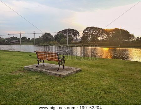 Wooden bench in public park. Public park in sunset time