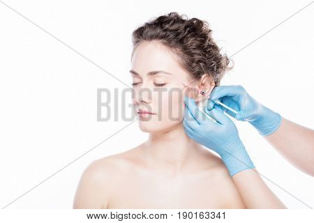 Aesthetic medicine. Young beautiful woman is having face injections. Anti-aging skincare and plastic surgery concept.