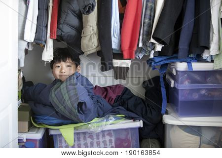 Chinese boy sitting on boxes in closet