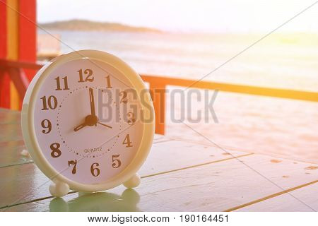 White clock at 8am on the sea background Freedom concept Sunshine effect Vintage filter