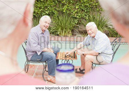 Older Caucasian men playing chess