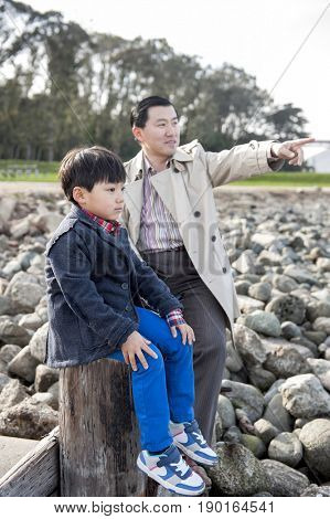Chinese father and son sitting on shore