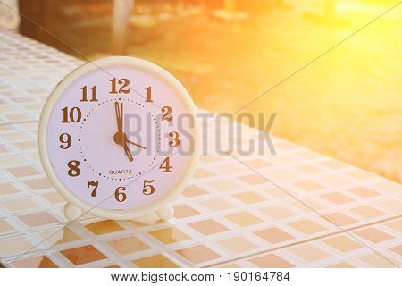 White clock at 5pm on the tiled floor and seashore background Freedom concept Sunshine effect Vintage tone