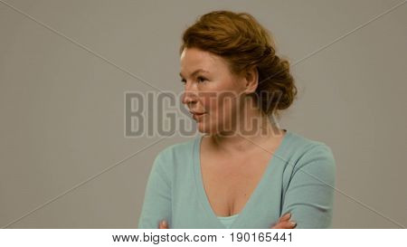 Mid aged female showing emotions of arrogance and despite. Foxy haired woman with despite and anger look in the studio close view. Toned footage.
