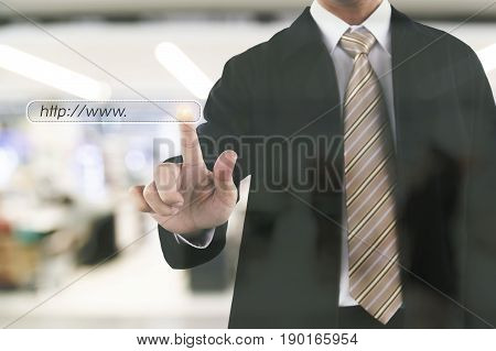 Businessman hand touching on web site to shopping. Blurry shopping mall in background.