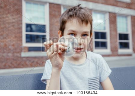 boy holds a fidget spinner in his hand. Spinning spinner and face of kid closeup on a schoolyard. Blurred background for a concept