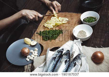 Woman cutting lemon for fish stuffing. Horizontal photo