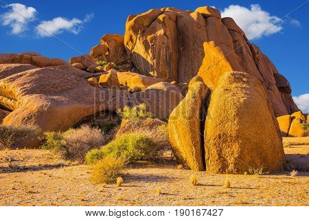 The massive granite outcrops in the Namib Desert. Play of light and shadow on the rocks. Stone of Spitzkoppe, Namibia. Concept of extreme and ecological tourism