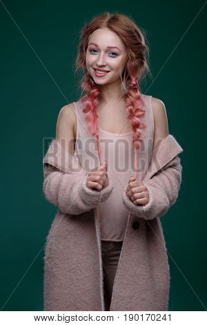 The Girl With Pink Hair In Braids, And Pink-blue Makeup With A Pink Coat Standing Against A Dark Bac