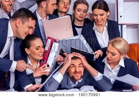 Mad business people office. Team people are unhappy with their leader. Intern man manager does not cope with his duties. Crazy crowd in stress throw up their chief's papers. New employee in team.