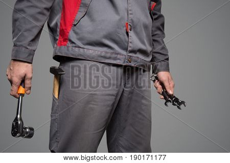 Serviceman holding tools in hands. Gray background.