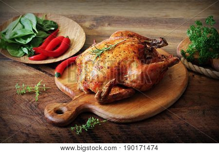 Whole roasted chicken with herb on cutting board . Vintage photo .