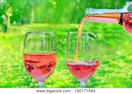 Rose wine being poured from a bottle into a glass at a picnic, with green grass and trees in the blurred background, with a place for text