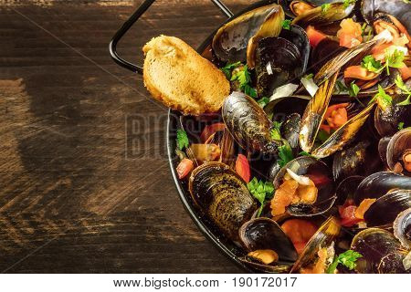 A closeup of a skillet of marinara mussels on a dark rustic background, with a toast, with a place for text