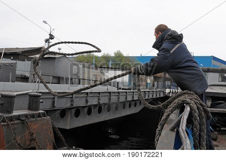 Murmansk, Russia - May 26, 2010: The sailor throws the mooring end from the ship's side onto the bollard
