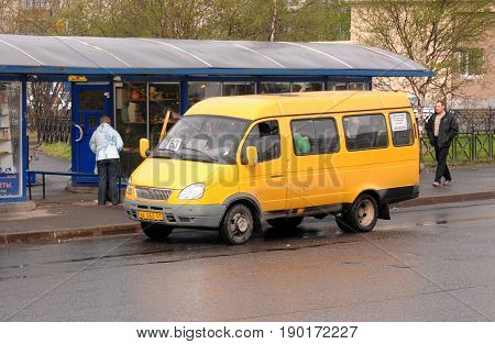Murmansk, Russia - May 25, 2010: Yellow shuttle bus at the bus stop
