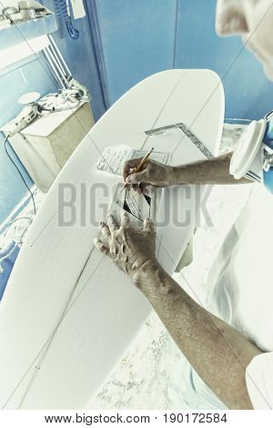 Craftsman making notes on surfboard in workshop