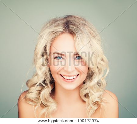 Happy Blonde Woman with Blonde Curly Hair. Smiling Fashion Model with Wavy Hairstyle