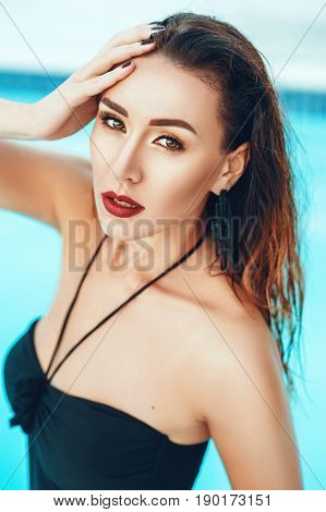 Close up portrait of Elegant sexy woman in black bikini on beautiful body is posing near the swimming pool in private villa. Sexuality beauty. Hot weather outside time to have rest and swim in pool.