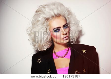 Portrait of young beautiful platinum blond woman with bold eyebrows and 80s style makeup