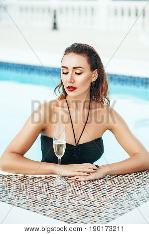 Elegant sexy woman in black bikini on the perfect body is posing near swimming pool with wineglass champagne in private villa. Sexuality beauty. Hot weather outside time to have rest and swim in pool.