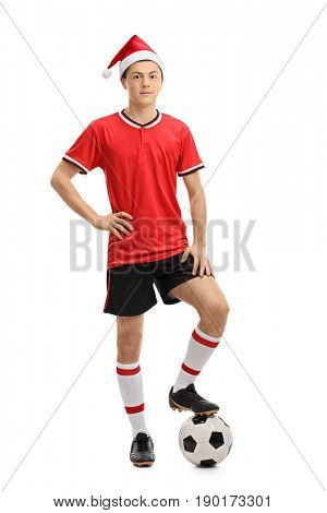 Full length portrait of a teenage soccer player wearing a Christmas hat and pressing a football isolated on white background