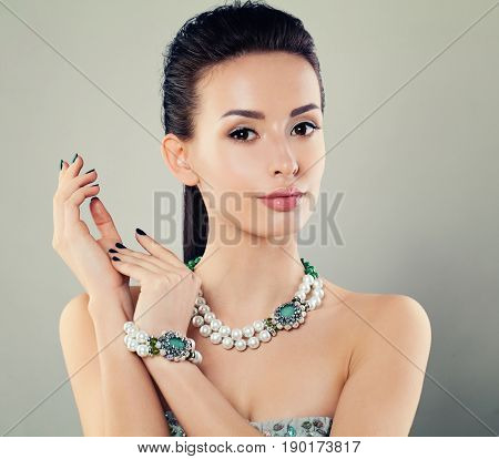Glamorous Woman with Jewelry Necklace and Bangle. Pearls and Green Crystals