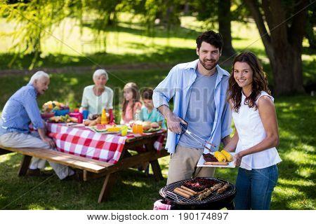 Portrait of smiling couple preparing barbeque in park