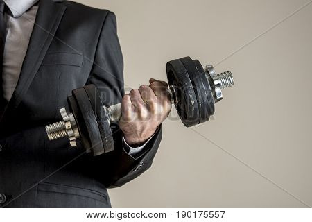 A businessman in business suit doing dumbbell biceps curl. Conceptual of determination and effort.
