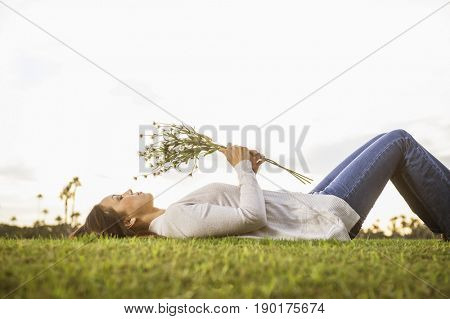 Woman with bouquet of flowers laying in grass