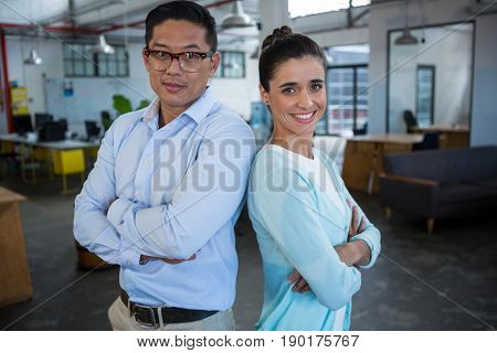 Portrait of smiling business colleagues standing back to back in office