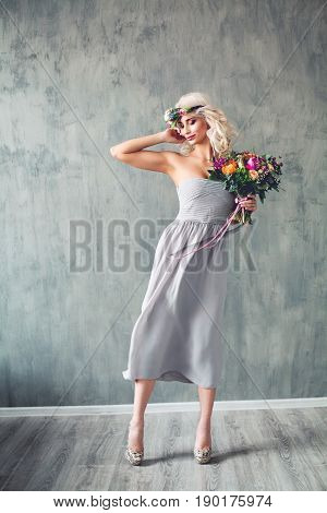 Beautiful Woman wearing Blowing Prom Dress. Perfect Model with Blonde Curly Hair and Flowers