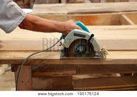 Circular saw cutting wood plank in carpentry workshop