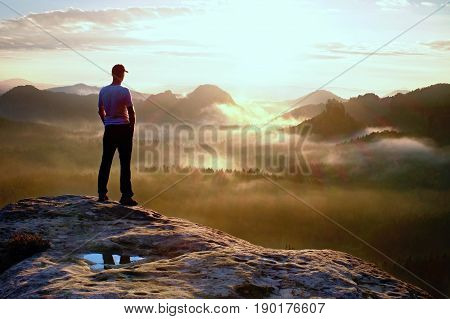 Alone Hiker In White Shirt And Red Cap Stand On Peak Of Rock In Rock Empires Park And Watch Over Mis