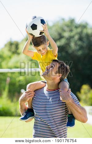 Smiling father carrying his son on shoulder at the park