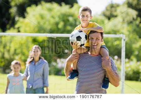 Portrait of smiling father carrying his son on shoulder at the park