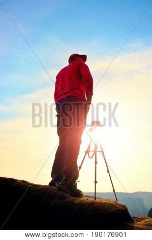 Photographer Stay With Tripod On Cliff And Thinking. Dreamy Fogy Landscape, Orange Misty Sunrise In