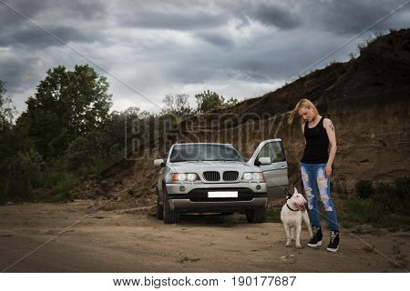 Brutal, daring girl with a fighting dog breed of bull terrier, near his car against the background of the rock