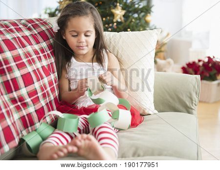 Hispanic girl making paper chain on sofa