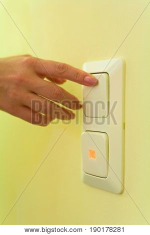 A woman's hand with a manicure presses the button of the switch.