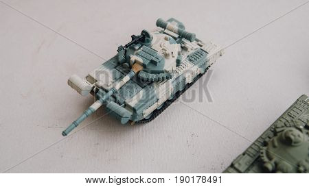 Toy Copies Of Tanks On A White Background Of Close-up. Historical Copies Of Soviet Tanks On The Tabl