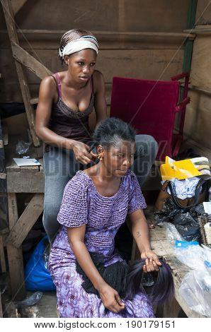 Original African hair braiding - Ivorian woman visiting a hairdresser at the Abidjan market. Abidjan, Cote d'Ivoire (Ivory Coast), Africa, April 2013.
