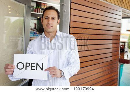 Hispanic man holding 'open' sign in door