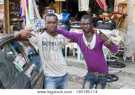 Two African male street vendors at the Abidjan market. Ivory Coast, May 2013.