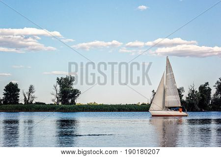 Yachts at sailing regatta. Beautiful ship yachts with white sails in the Dnieper river on a background of the blue sky with clouds. Sailing yacht race. Yachting outdoor lifestyle.