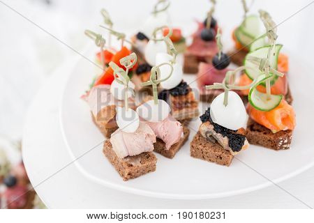 the buffet at the reception. Assortment of canapes. Banquet service. catering food, snacks with fish, vegetables and meat. rye, wheat bread