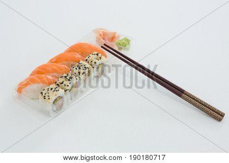 Plate of nigiri and uramaki sushi with chopstick on white background